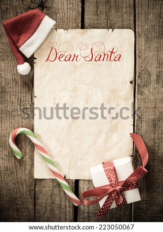 Child letter to Santa Claus. Christmas decorations and old paper with place for greeting on old paper blackboard.  - stock photo