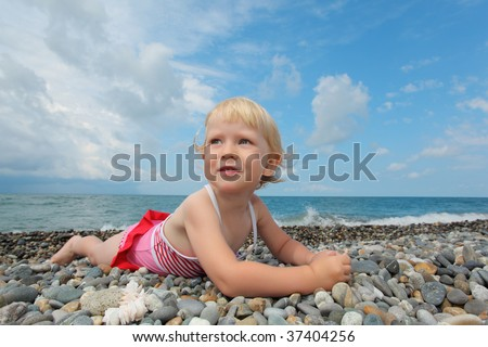 child lies on pebble beach - stock photo