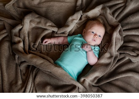 child little boy is lying in bed under a brown blanket - stock photo
