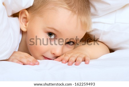 child little boy is lying in bed under a white blanket  - stock photo