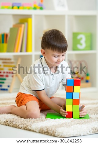 Child little boy playing with wooden cubes, smiling - stock photo