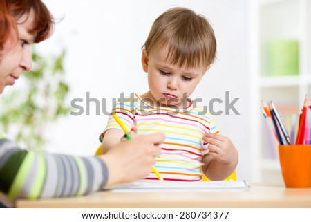 child little girl drawing with pencils in preschool - stock photo