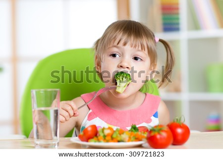 Child little girl eats vegetable salad using fork - stock photo