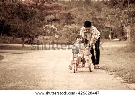 Child little girl having fun to ride tricycle with family, Father is pushing tricycle, vintage color filter - stock photo