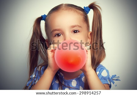 child little girl in a blue dress inflates a red balloon - stock photo