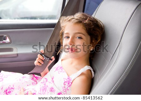 child little girl indoor car putting safety belt smiling - stock photo