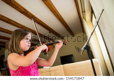 Child (little girl) playing violin indoors at home - stock photo