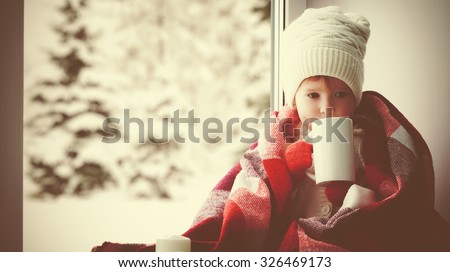 child little girl sitting by the window with a cup of hot tea and looking at the winter forest - stock photo