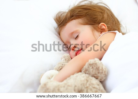 child little girl sleeps in the bed with a toy teddy bear - stock photo