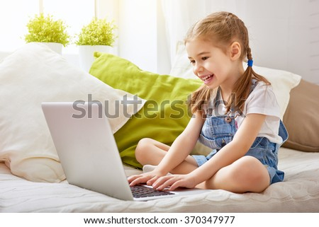Child little girl with a laptop computer at home. Happy little child plays indoors using pc. - stock photo