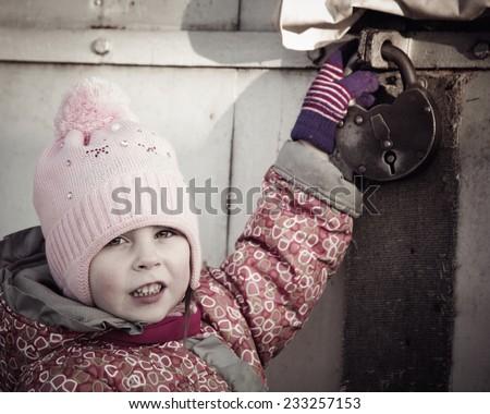 child locked behind a metallic gate - stock photo
