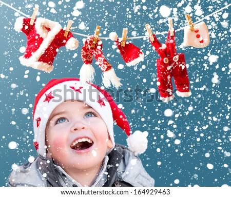 Child looking at Santa Claus clothes on rope - stock photo