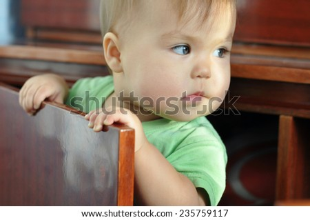 Child looking away and hiding in the cupboard - stock photo