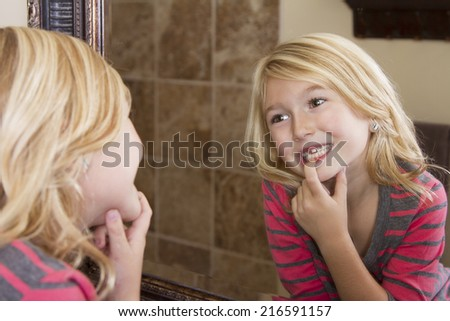 Child looking in mirror and pointing at missing front tooth - stock photo