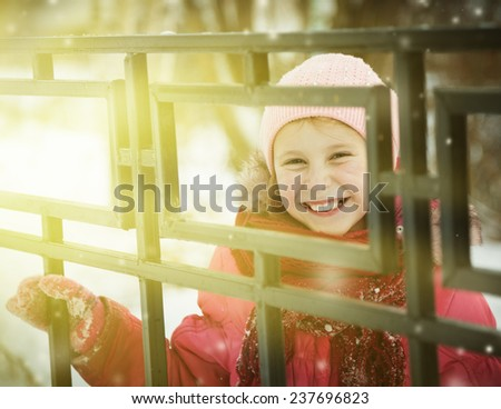 Child looking out of locked wire fencing outdoors - stock photo