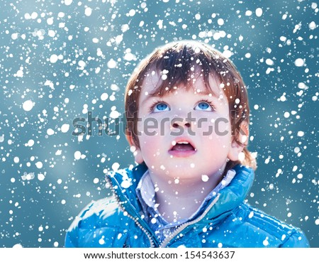 Child looking snow falling with his mouth open - stock photo