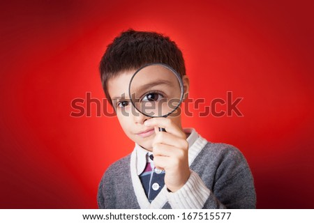 Child looking through a magnifying glass against red background. - stock photo