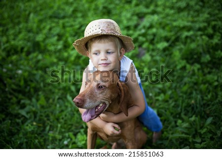 Child love his dog. Outdoor portrait - stock photo