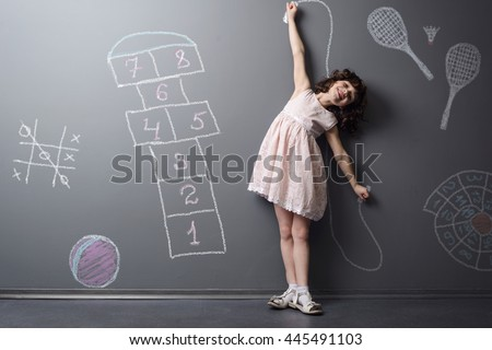 Child loves to be active and smiles while doing sports. Depicted childish favorite games like hopscotch, badminton and jumping rope on the neutral background in the studio. - stock photo