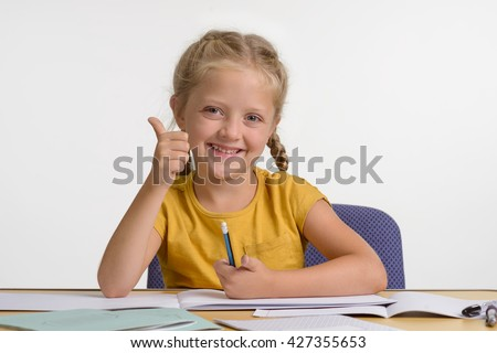 Child loves to learn new information, interesting facts. She shows the gesture OK and smiles with very positive look. Young girl in library. Professional retouching of the photo. - stock photo