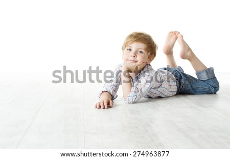 Child lying down on floor, Kid Boy over white background, looking at camera - stock photo