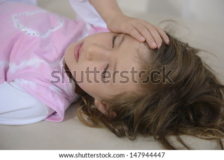 Child lying down suffering from a headache - stock photo