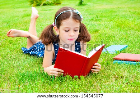 Child lying on grass and reading a book - stock photo