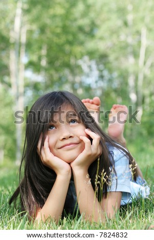 Child lying on grass looking up with thoughtful expression. Part asian, scandinavian background. - stock photo