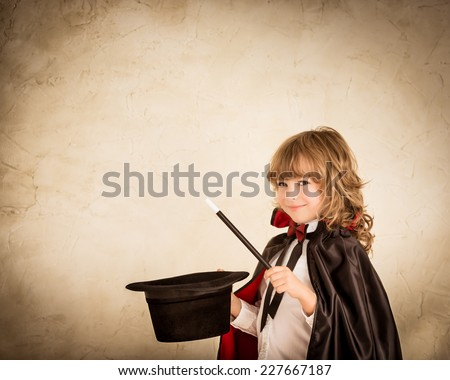 Child magician holding top hat and magic wand. Success concept - stock photo