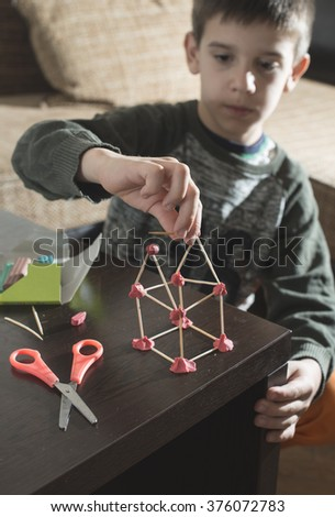 Child make house with wooden sticks and plasticine - stock photo