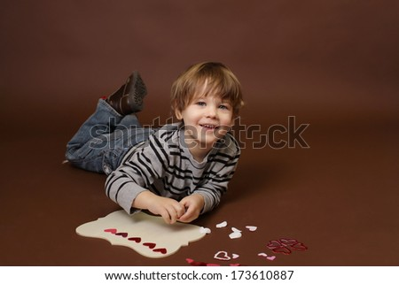 Child making  Valentine's Day Craft with Heart stickers - stock photo