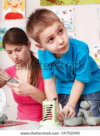 Child  mould from clay with teacher. Child care. - stock photo