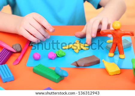 Child moulds from plasticine on table - stock photo