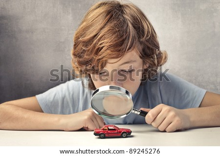 Child observing a toy-car through a magnifying glass - stock photo