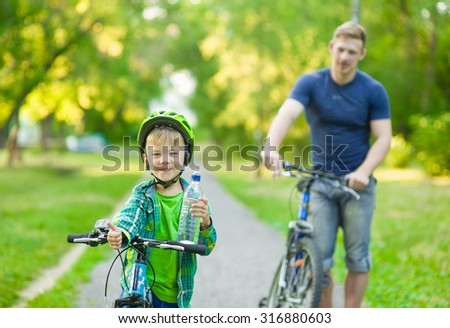 child on a bicycle drink water with father in the park - stock photo
