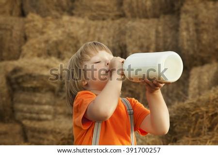 child on a haystack drink milk of bottle - stock photo