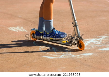 Child on a Scooter / Feet of a child with sneakers on a metal scooter. Pavement with drawings made with chalk - stock photo