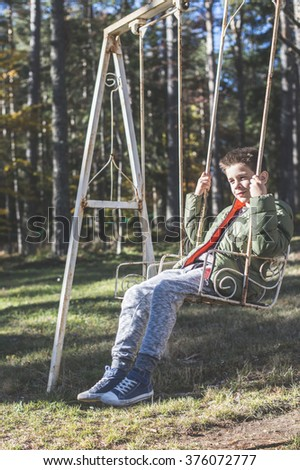 Child on a swing in a forest - stock photo