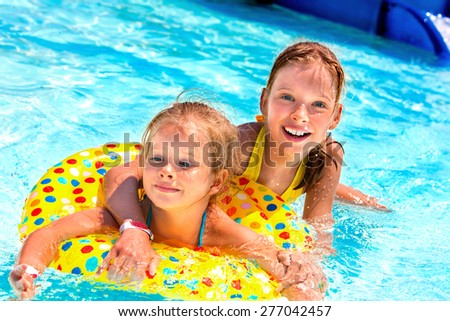 Child on beach ring in swimming pool. - stock photo