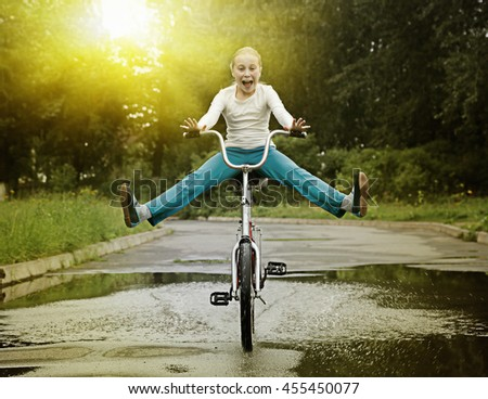 Child on bike driving through a puddle. - stock photo
