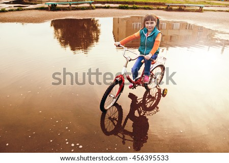 Child on bike rides through a puddle in autumn day. - stock photo