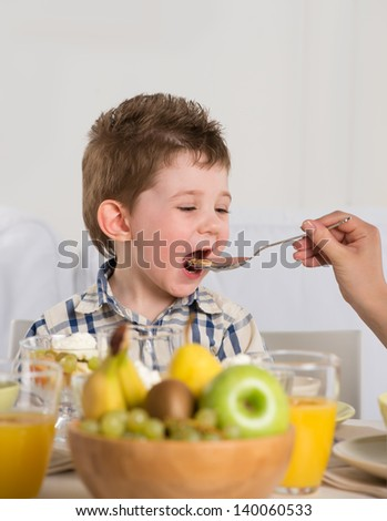 Child on breakfast - parent feeding son from spoon - stock photo