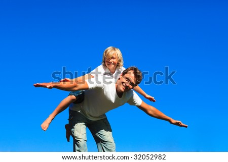 Child on father's back playing airplane outdoors - stock photo
