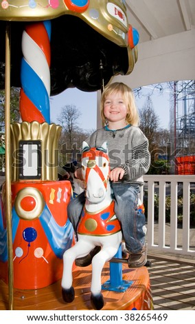 child on merry-go-round horse carousel. happy child on ride in fairground park - stock photo