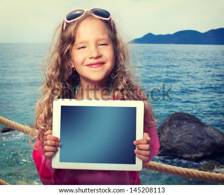 Child on the beach with tablet computer. Girl showing screen digital pc - stock photo
