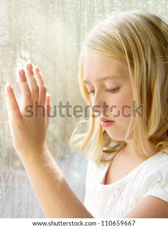 Child or teen looking down with hand on a rainy window - stock photo