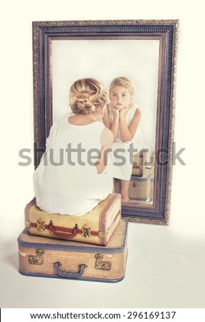 Child or young girl staring at herself in a mirror, sitting on vintage luggage, with a fish tail braid in her hair. Vintage or retro filter applied. - stock photo