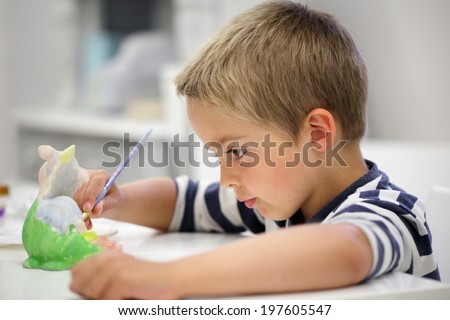 Child painting a ceramic pottery model at school concept for art and creative education - stock photo