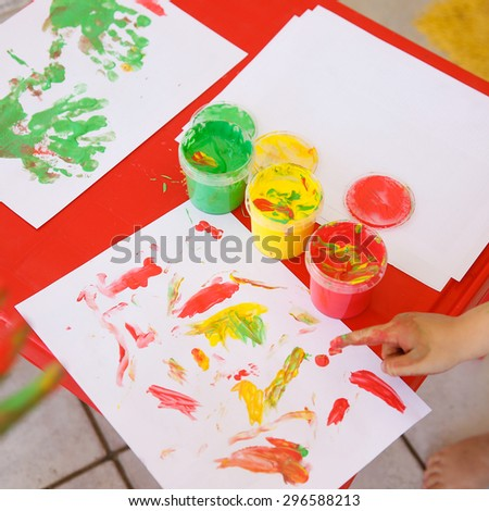 Child painting a drawing with finger paints, used for finger drawing and sensory play. Fun childhood, sensory and experience-based learning concept.  - stock photo