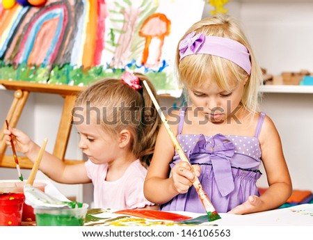 Child painting at easel in school. Education. - stock photo